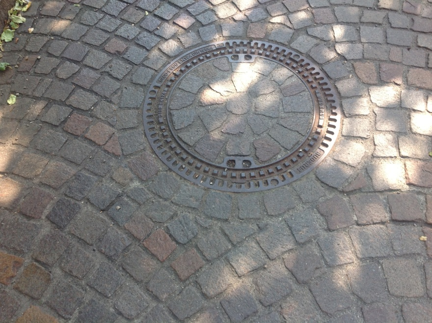 Manhole cover surrounded by well placed cobblestones