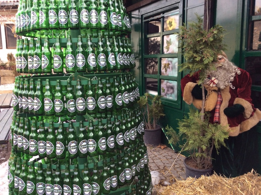 "Santa and a ""tree"" made of empty beer bottles."