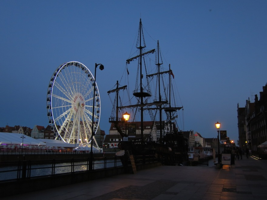 The Pirate Ship by night, with ferris wheel across the harbor.