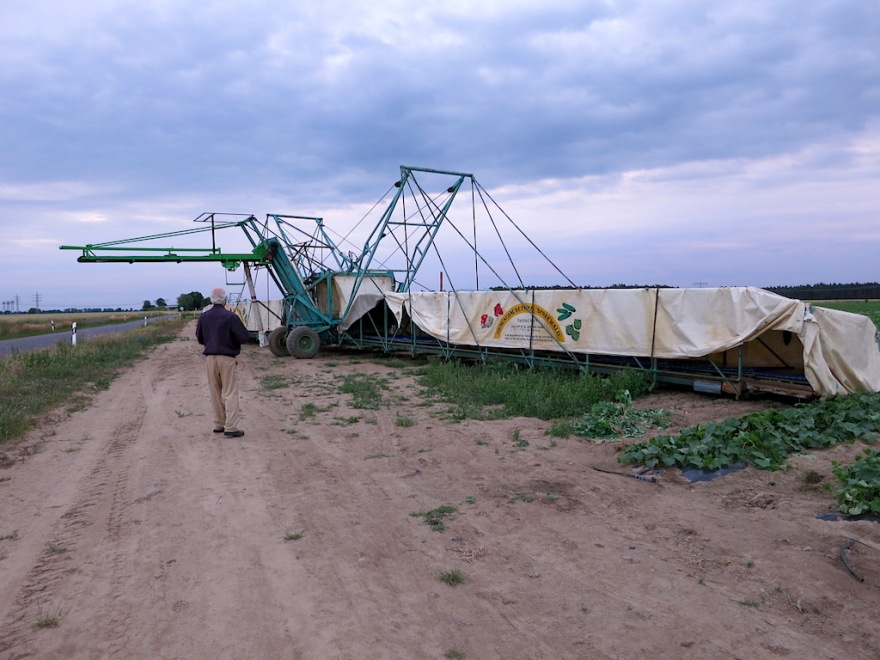 The harvester is a large machine with wings on both sides, pulled by a tractor.
