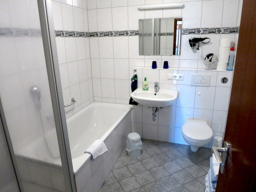 Large bathroom with tub and shower with the usual inadequate place to put things.
