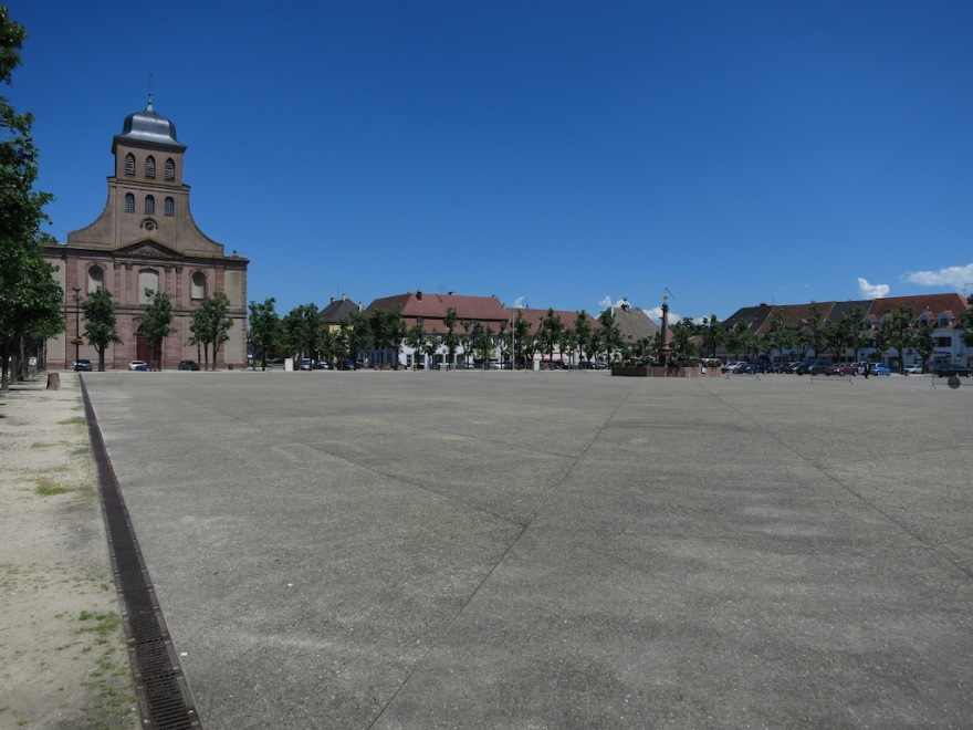 The barren market square, hot and desolate.